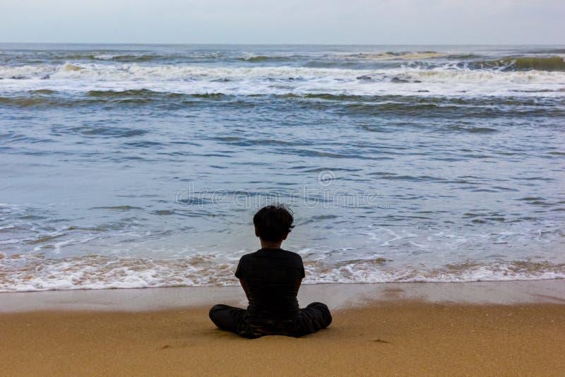 Συνεδρίαση παιδιών που απομονώνεται σε μια άποψη παραλιών από πίσω, την έννοια της μοναξιάς και μόνο στοκ φωτογραφίες με δικαίωμα ελεύθερης χρήσης