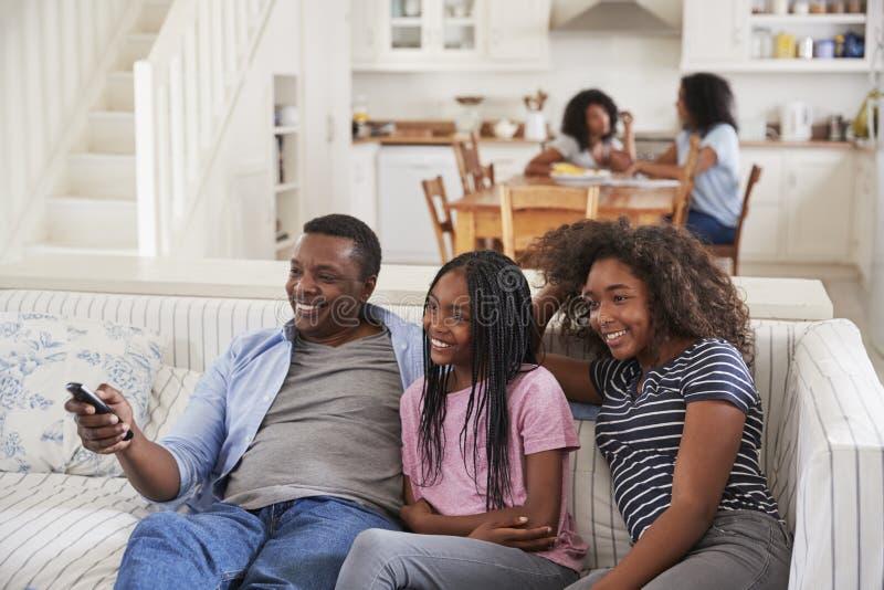 Συνεδρίαση πατέρων στον καναπέ που προσέχει τη TV με τα έφηβη κόρη στοκ φωτογραφίες