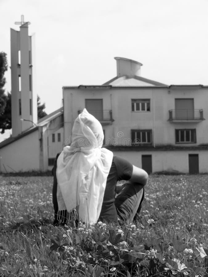 Συνεδρίαση προσώπων στη χλόη που φορά ένα άσπρο μαντίλι στο κεφάλι του που αντιμετωπίζει ένα κτήριο στο υπόβαθρο στοκ εικόνα