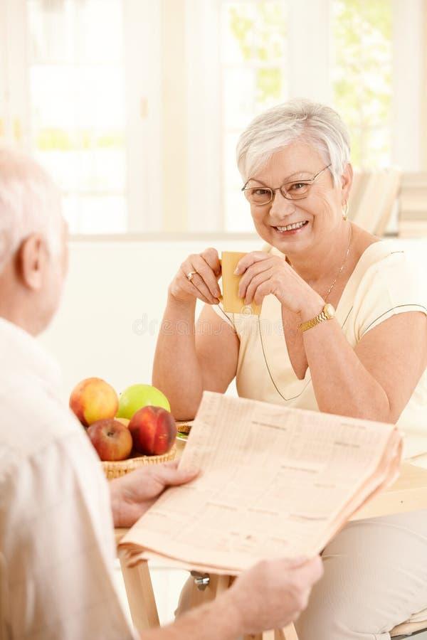 Συνεδρίαση συζύγων χαμόγελου ηλικιωμένη στον πίνακα με την κούπα στοκ φωτογραφία με δικαίωμα ελεύθερης χρήσης
