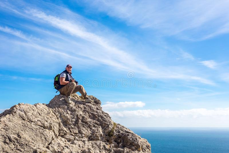 Συνεδρίαση τουριστών πάνω από το βουνό που εξετάζει την απόσταση στοκ εικόνες με δικαίωμα ελεύθερης χρήσης