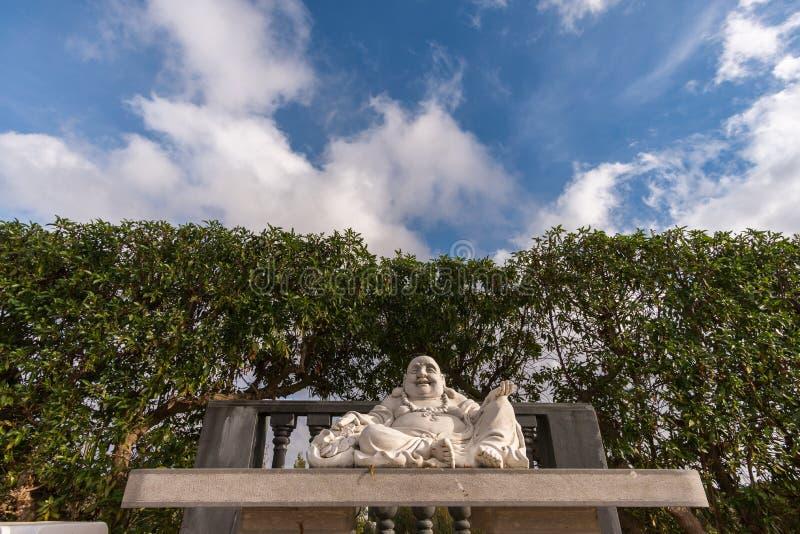 Συνεδρίαση του Βούδα κάτω από έναν νεφελώδη ουρανό στοκ εικόνες