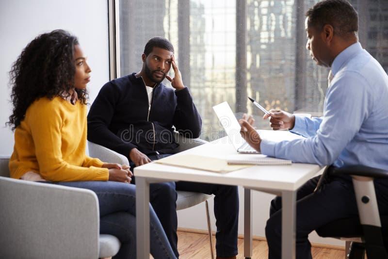 Συνεδρίαση του ζεύγους με τον αρσενικό οικονομικό σύμβουλο σχέσης συμβούλων στην αρχή στοκ φωτογραφία