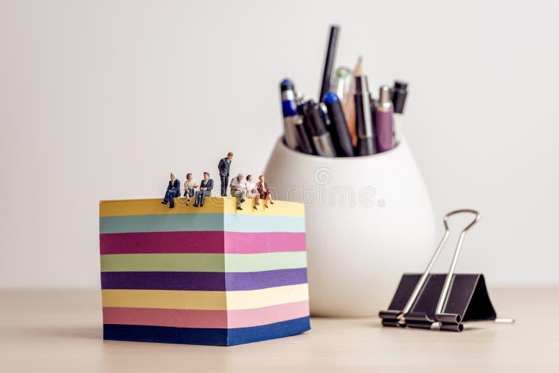 Συνεδρίαση του Businesspeople σε ένα μικροσκοπικό γραφείο στοκ φωτογραφία με δικαίωμα ελεύθερης χρήσης