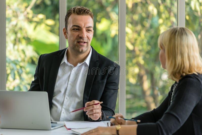 Συνεδρίαση των επιχειρηματιών με το συνάδελφό του στο γραφείο αιθουσών συνεδριάσεων στοκ εικόνες