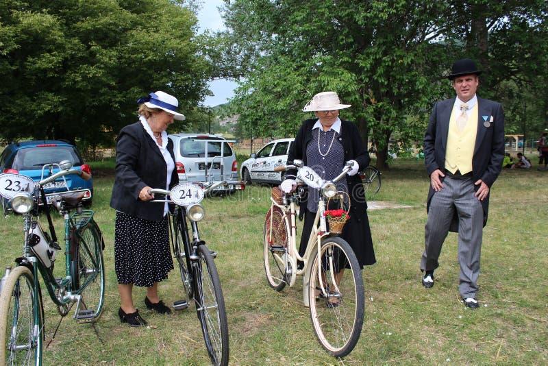 Συνεδρίαση των ιστορικών ποδηλάτων - μια κυρία σε ένα εκλεκτής ποιότητας κοστούμι με το αντίστοιχο ποδήλατο στοκ φωτογραφίες