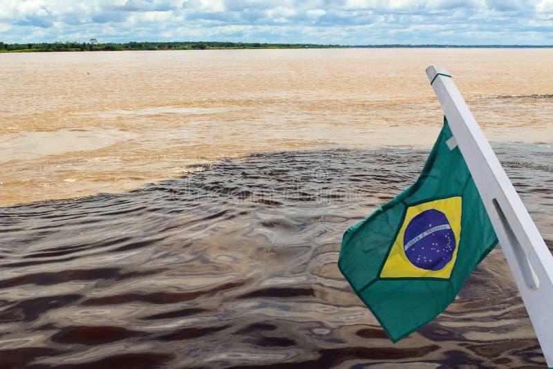 Συνεδρίαση των νερών του νέγρου και του Αμαζονίου του Ρίο με τη σημαία στοκ εικόνες με δικαίωμα ελεύθερης χρήσης