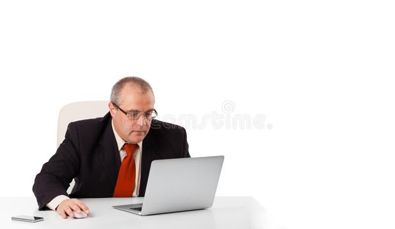 Συνεδρίαση Buisnessman στο γραφείο και να φανεί lap-top με το διάστημα αντιγράφων στοκ εικόνα με δικαίωμα ελεύθερης χρήσης