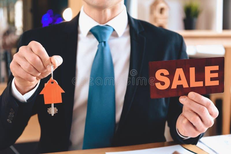 Συνεδρίαση Realtor στο γραφείο στην αρχή Το Realtor κρατά το σημάδι πώλησης και το εικονίδιο διακοπής του σπιτιού στοκ εικόνες