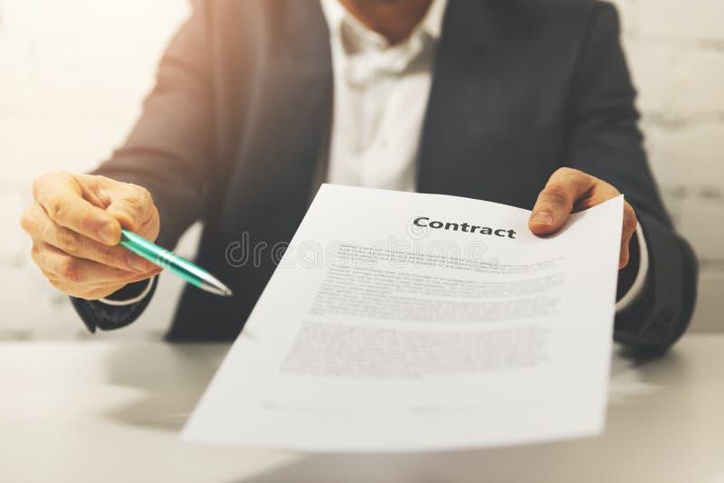 Συνεργασία - επιχειρηματίας που δίνει την επιχειρησιακή σύμβαση για να υπογράψει στοκ εικόνα με δικαίωμα ελεύθερης χρήσης