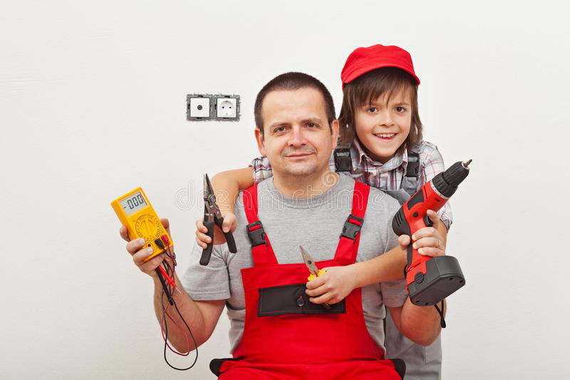 Συνεργασία με τον μπαμπά - ευτυχές αγόρι που βοηθά τον πατέρα του στοκ εικόνες