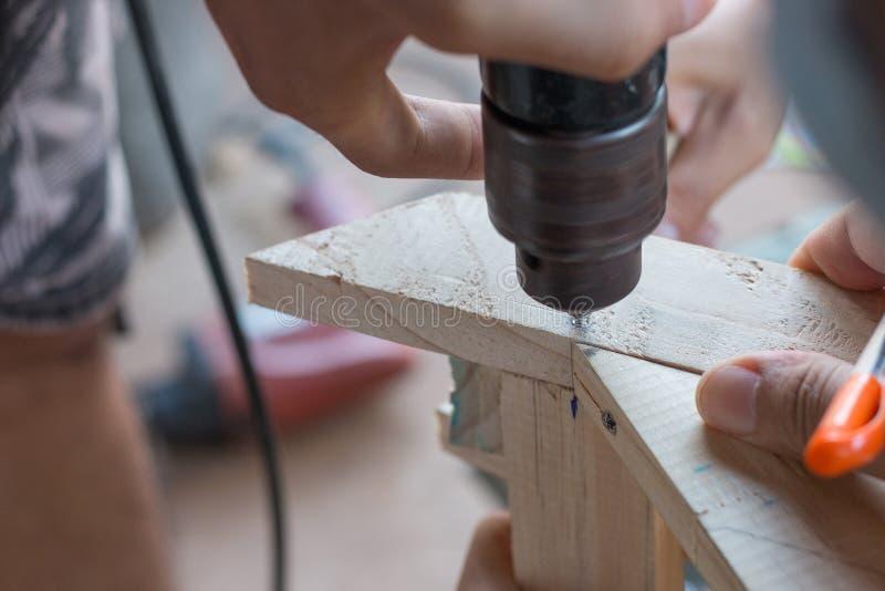 Συνεργαστείτε στη διάτρυση της ξυλουργικής με το ηλεκτρικό τρυπάνι στοκ εικόνες