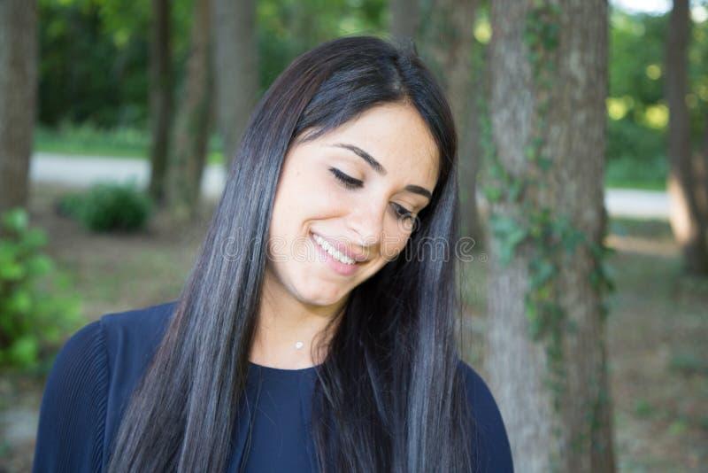 Συνεσταλμένο brunette γυναικών ομορφιάς υπαίθριο με τα δέντρα στοκ εικόνες