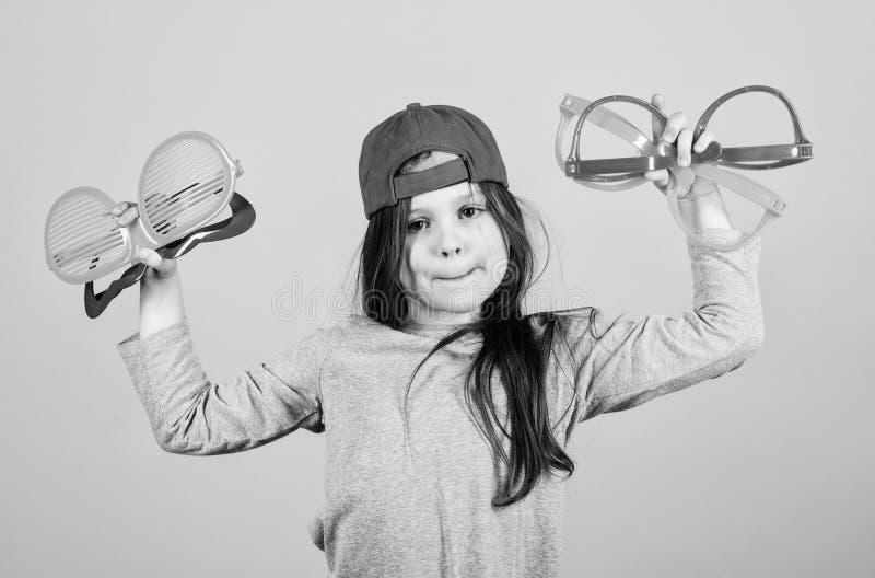 Συνεχίστε Μοντέρνο κορίτσι κομμάτων Λατρευτό κορίτσι κομμάτων που κρατά τα φανταχτερά γυαλιά Χαριτωμένο μικρό παιδί που επιλέγει  στοκ εικόνα με δικαίωμα ελεύθερης χρήσης