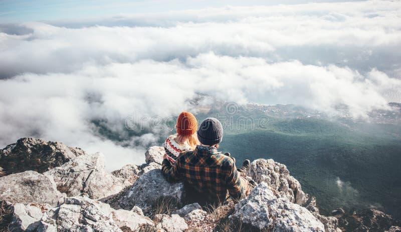 Συνεδρίαση ανδρών και γυναικών ζεύγους στον απότομο βράχο που απολαμβάνει τα βουνά στοκ εικόνες