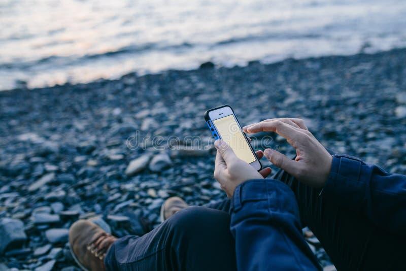 Συνεδρίαση ατόμων στην παραλία και χρησιμοποίηση ενός τηλεφώνου κυττάρων στοκ φωτογραφία