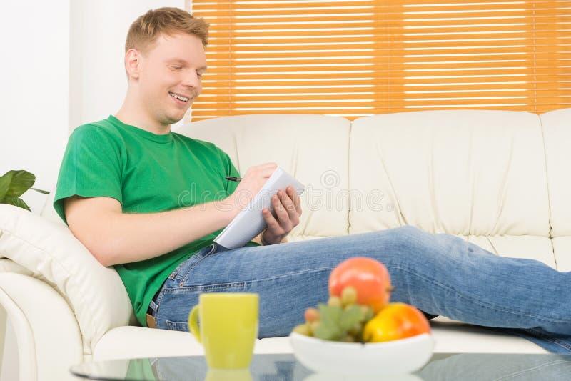 Συνεδρίαση ατόμων στον καναπέ και την επιστολή γραψίματος στοκ φωτογραφία με δικαίωμα ελεύθερης χρήσης