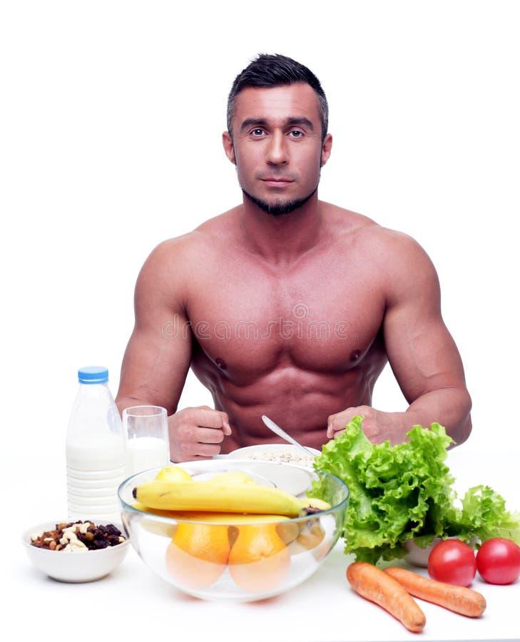 Συνεδρίαση ατόμων στον πίνακα με τα υγιή τρόφιμα στοκ φωτογραφία με δικαίωμα ελεύθερης χρήσης