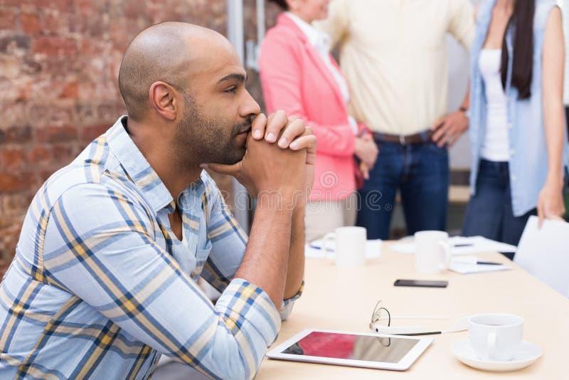 Συνεδρίαση ατόμων στο γραφείο που χρησιμοποιεί την ταμπλέτα του στοκ φωτογραφία