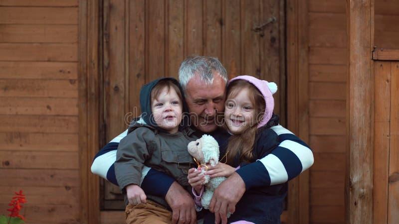 Συνεδρίαση αδελφών και αδελφών στα γόνατα παππούδων s Ο ηληκιωμένος αγκαλιάζει τον εγγονό και την εγγονή του 4K στοκ φωτογραφίες με δικαίωμα ελεύθερης χρήσης
