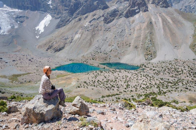 Συνεδρίαση γυναικών κοντά στη λίμνη στα βουνά στοκ φωτογραφία