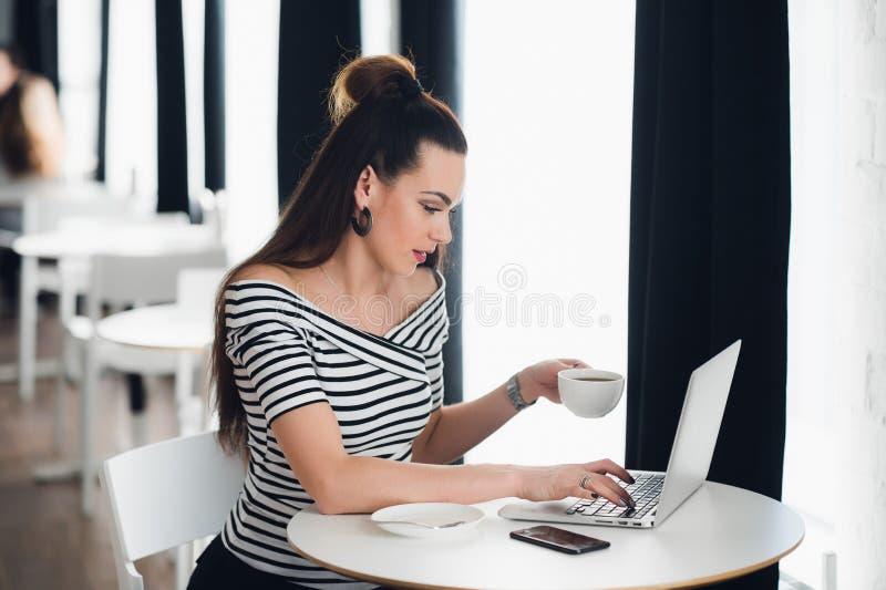 Συνεδρίαση γυναικών κοντά στο παράθυρο σε έναν καφέ με ένα lap-top Ενήλικο θηλυκό που κρατά ένα φλυτζάνι και που εξετάζει την οθό στοκ εικόνες