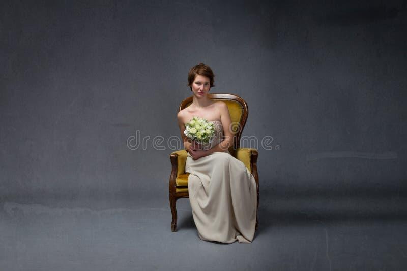 Συνεδρίαση γυναικών νυφών στον κίτρινο καναπέ στοκ φωτογραφία