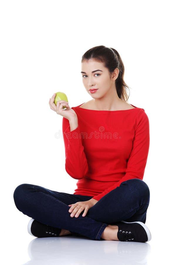 Συνεδρίαση γυναικών που κρατά cross-legged ένα μήλο στοκ εικόνες
