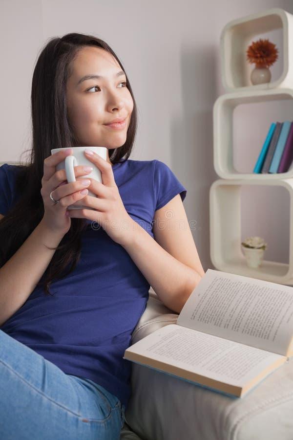 Συνεδρίαση γυναικών σκέψης ασιατική στην κούπα εκμετάλλευσης καναπέδων του καφέ στοκ εικόνα