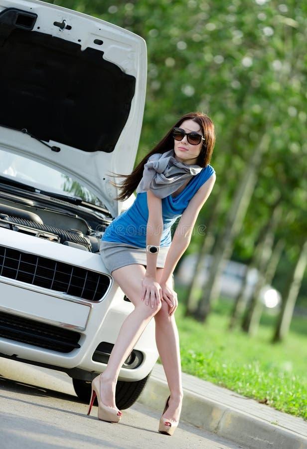 Συνεδρίαση γυναικών στην κουκούλα του σπασμένου αυτοκινήτου στοκ εικόνες με δικαίωμα ελεύθερης χρήσης