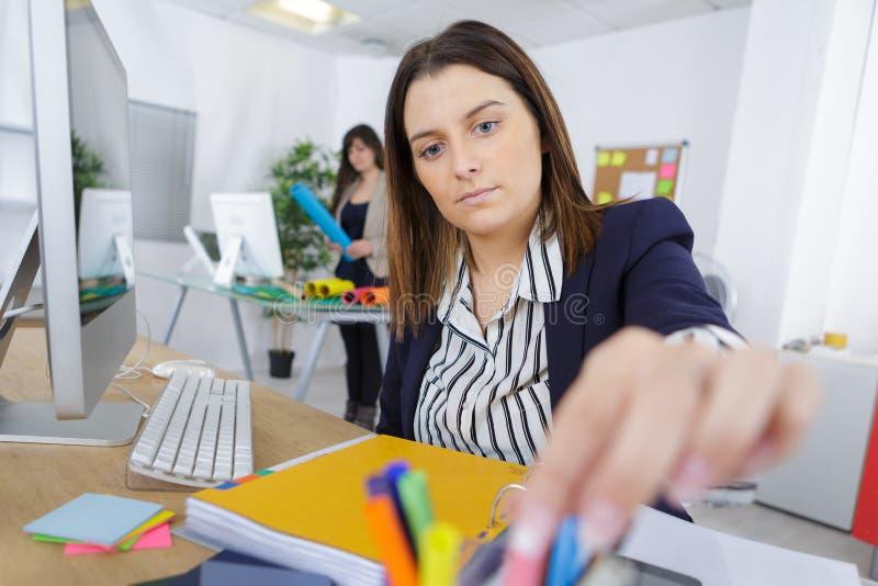 Συνεδρίαση γυναικών στο γραφείο στην αρχή στοκ εικόνα