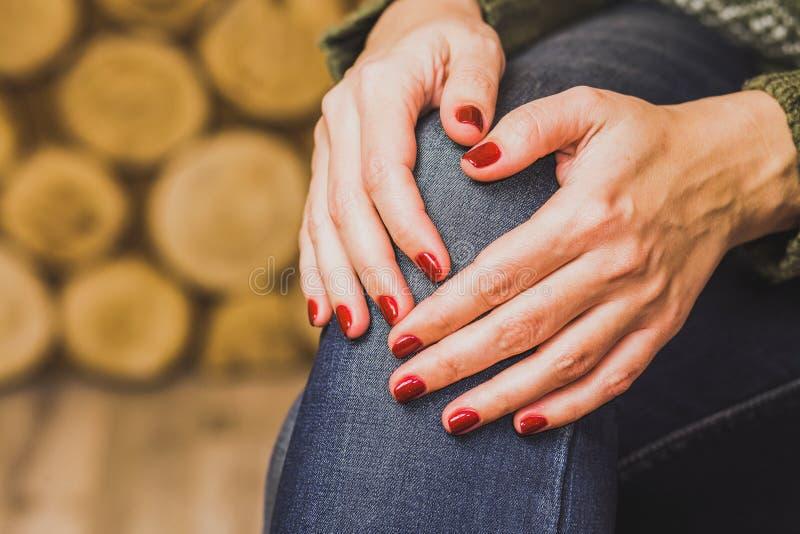 Συνεδρίαση γυναικών στο εσωτερικό με τα χέρια της στο γόνατο στοκ εικόνα