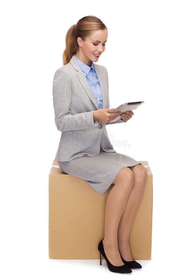 Συνεδρίαση γυναικών στο κουτί από χαρτόνι με το PC ταμπλετών στοκ φωτογραφία με δικαίωμα ελεύθερης χρήσης