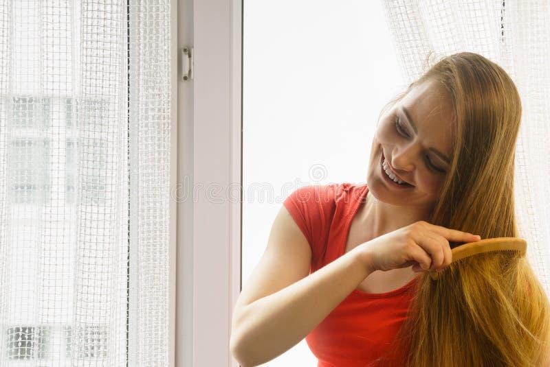Συνεδρίαση γυναικών στο windowsill που βουρτσίζει την τρίχα της στοκ εικόνες