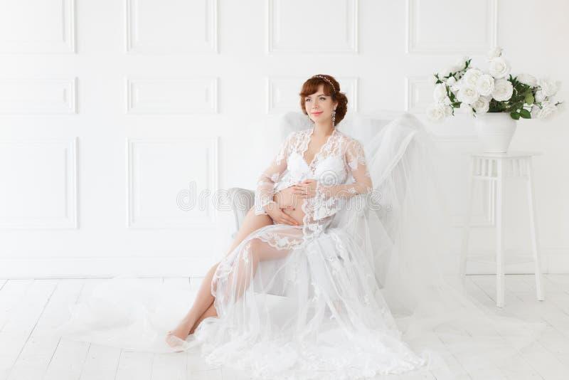 Συνεδρίαση εγκύων γυναικών σε μια καρέκλα σε ένα όμορφο άσπρο μπουντουάρ φορεμάτων στοκ φωτογραφία με δικαίωμα ελεύθερης χρήσης