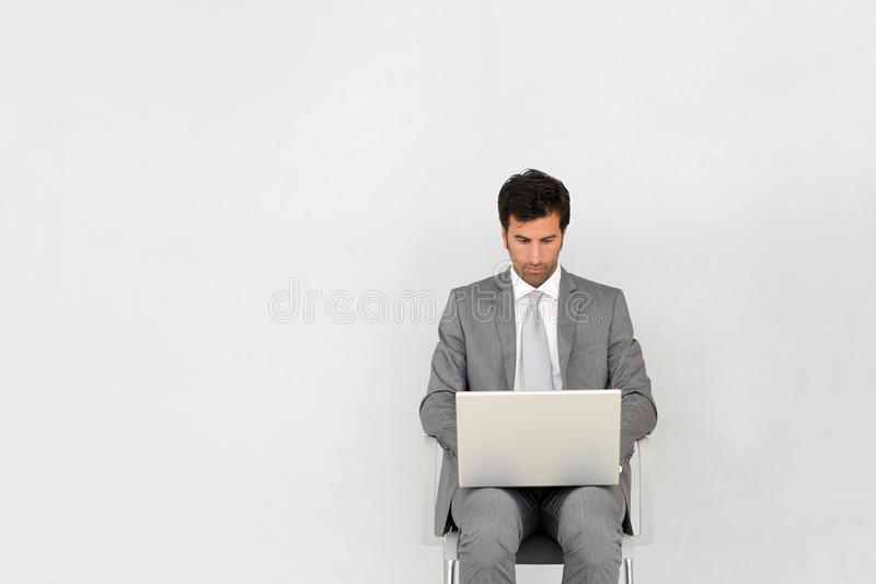 Συνεδρίαση επιχειρηματιών στη αίθουσα αναμονής που χρησιμοποιεί το lap-top στοκ εικόνες