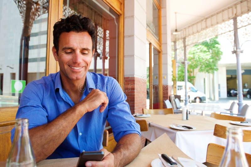 Συνεδρίαση επιχειρηματιών στον υπαίθριο καφέ με το κινητό τηλέφωνο στοκ φωτογραφία με δικαίωμα ελεύθερης χρήσης