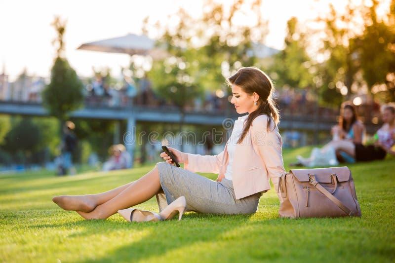 Συνεδρίαση επιχειρηματιών στο πάρκο που ελέγχει το smartphone της, ηλιόλουστο ποσό στοκ φωτογραφία με δικαίωμα ελεύθερης χρήσης