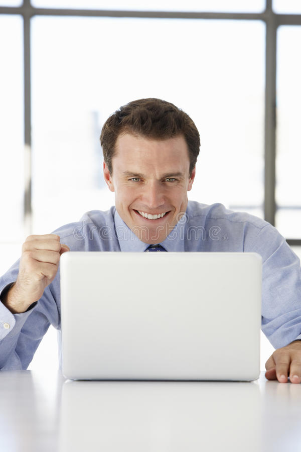 Συνεδρίαση επιχειρηματιών στο στην αρχή χρησιμοποιώντας lap-top γραφείων στοκ εικόνα