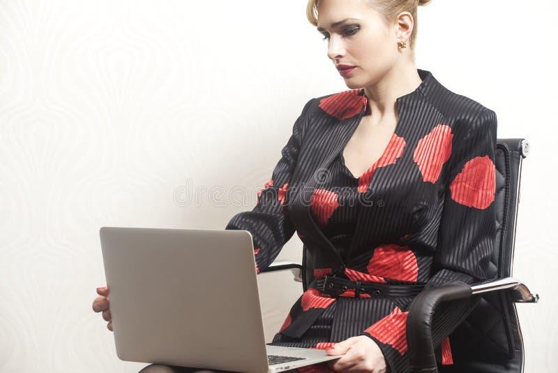 Συνεδρίαση επιχειρησιακών γυναικών στην καρέκλα με το σημειωματάριο ι στοκ εικόνες