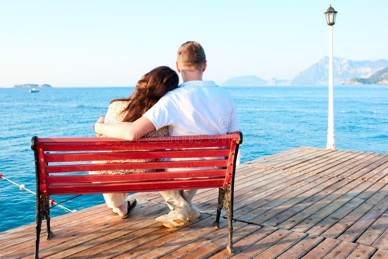 Συνεδρίαση ζευγών αγάπης στον πάγκο με το αγκάλιασμα θάλασσας στοκ εικόνα