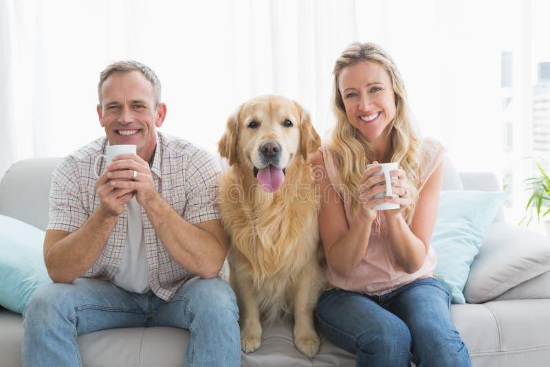 Συνεδρίαση ζευγών χαμόγελου περιστασιακή στον καναπέ που έχει τον καφέ στοκ φωτογραφία με δικαίωμα ελεύθερης χρήσης