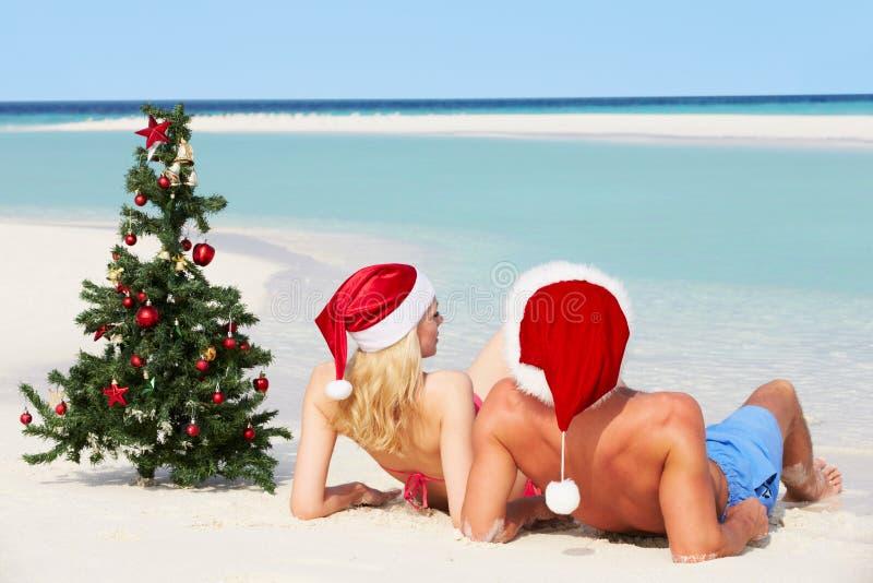 Συνεδρίαση ζεύγους στην παραλία με το χριστουγεννιάτικο δέντρο και τα καπέλα στοκ εικόνα με δικαίωμα ελεύθερης χρήσης