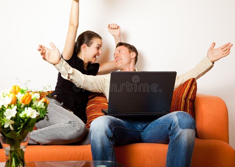 Συνεδρίαση ζεύγους στον καναπέ με ένα lap-top στοκ εικόνες