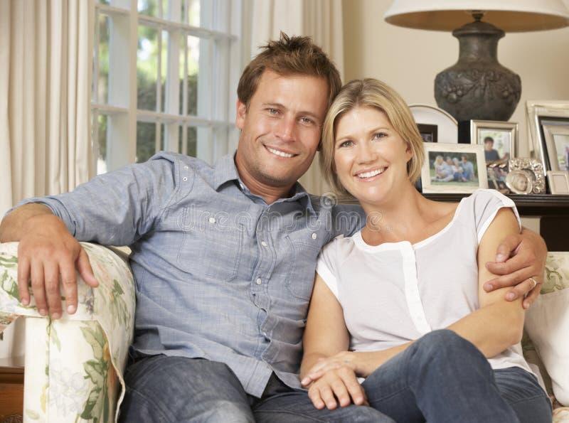 Συνεδρίαση ζεύγους στον καναπέ στο εσωτερικό στοκ φωτογραφία με δικαίωμα ελεύθερης χρήσης