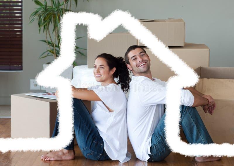 Συνεδρίαση ζεύγους στο καθιστικό ενάντια στην περίληψη σπιτιών στο υπόβαθρο στοκ εικόνες