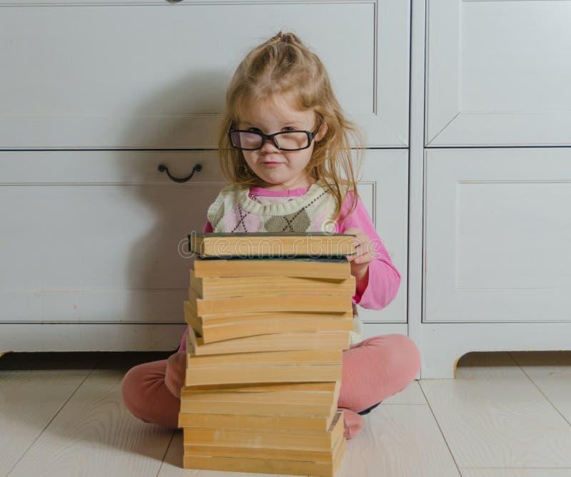 Συνεδρίαση κοριτσάκι στο πάτωμα με το σωρό των βιβλίων με τα γυαλιά στοκ φωτογραφία με δικαίωμα ελεύθερης χρήσης