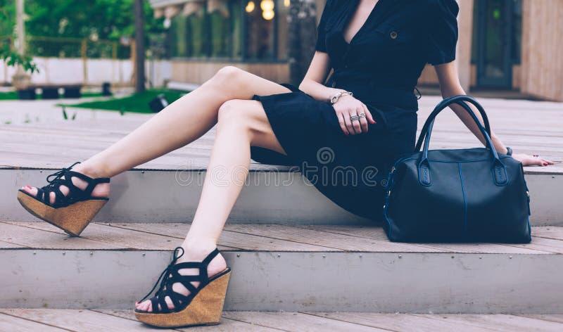 Συνεδρίαση κοριτσιών στα σκαλοπάτια με μεγάλες μαύρες έξοχες μοντέρνες τσάντες σε ένα φόρεμα και υψηλά σανδάλια σφηνών σε ένα θερ στοκ εικόνα με δικαίωμα ελεύθερης χρήσης