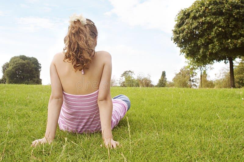 Συνεδρίαση κοριτσιών στη χλόη στο πάρκο. στοκ εικόνα με δικαίωμα ελεύθερης χρήσης