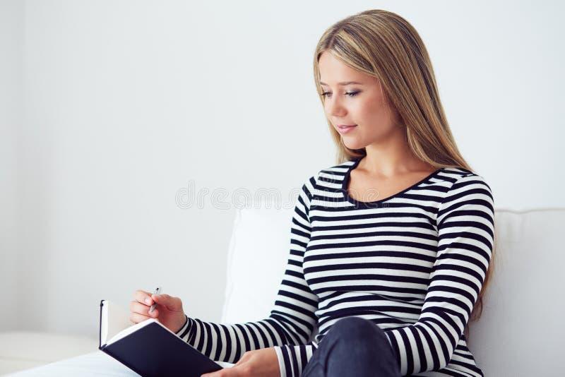 Συνεδρίαση κοριτσιών στον καναπέ και γράψιμο σε ένα ημερολόγιο στοκ φωτογραφία με δικαίωμα ελεύθερης χρήσης